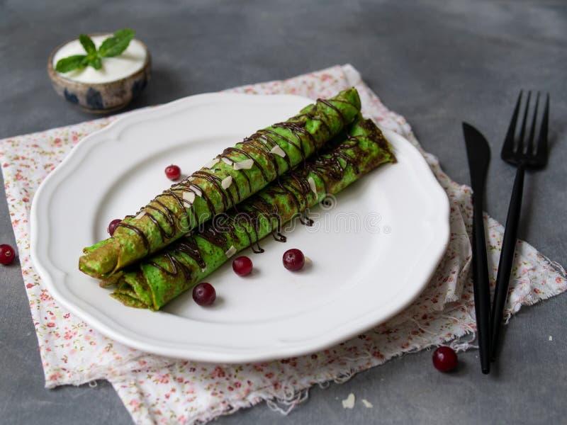 Crepes finos da hortelã da cor verde, torcidos nos tubos, com molho de chocolate, creme de leite, folha da hortelã e pétalas da a imagens de stock