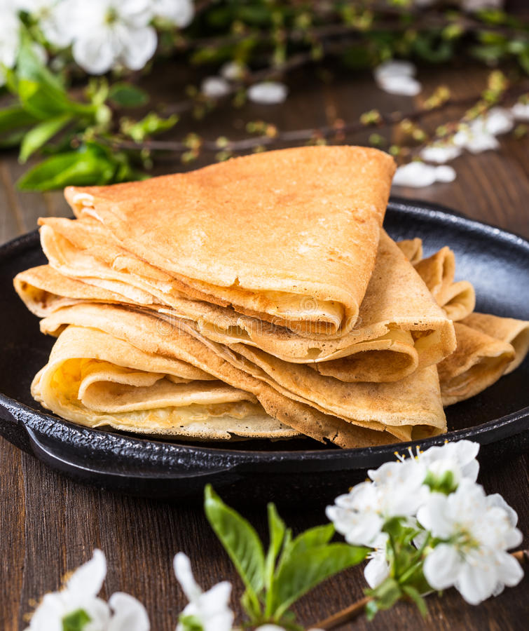 Crepes folded in triangles on frying pan. Homemade crepes folded in triangles on frying pan on spring blossom background stock photos