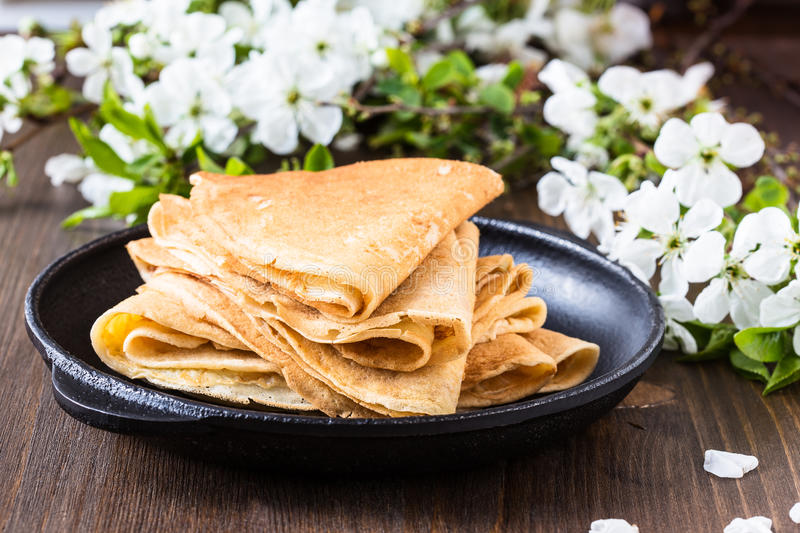 Crepes folded in triangles on frying pan. Homemade crepes folded in triangles on frying pan on spring blossom background royalty free stock image
