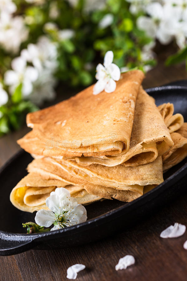 Crepes folded in triangles on frying pan. Homemade crepes folded in triangles on frying pan on spring blossom background stock image