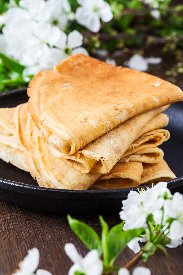 Crepes folded in triangles in frying pan. Homemade crepes folded in triangles in frying pan on spring blossom background stock image