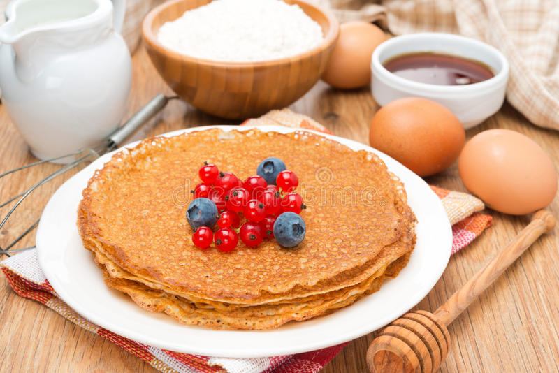 Crepes with fresh berries and ingredients for baking on table. Crepes with fresh berries and ingredients for baking on a wooden table, close-up stock photos