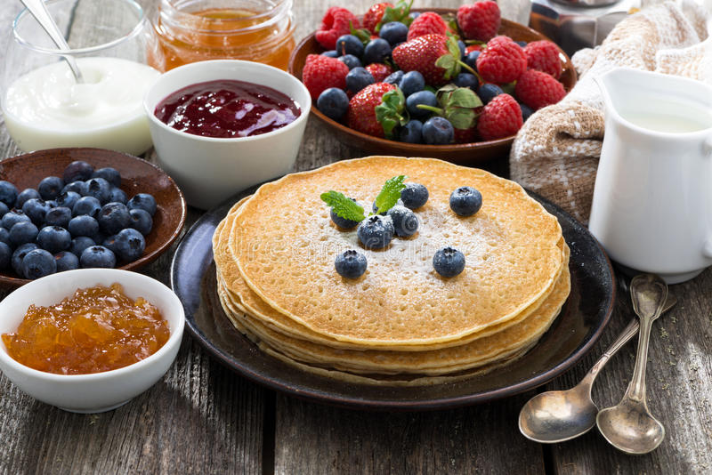 Crepes, fresh berries and jams on wooden table royalty free stock images