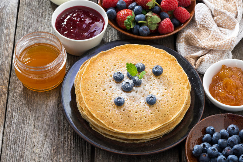 Crepes, fresh berries and jams on wooden table, top view stock photography