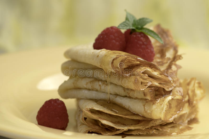Crepes with fresh rasberries and honey. Serving French Crepes with fresh rasberries and honey on the plate. Close up royalty free stock image