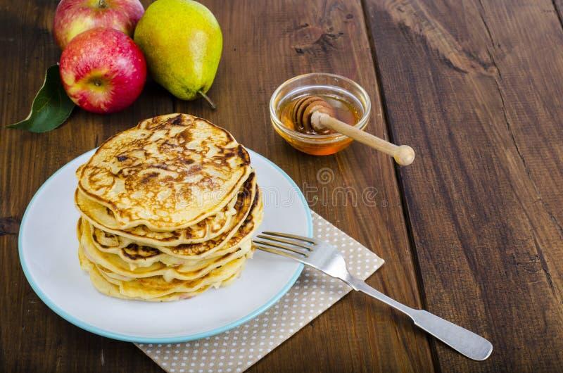 Crepes fritas calientes con las manzanas y la miel imagen de archivo libre de regalías