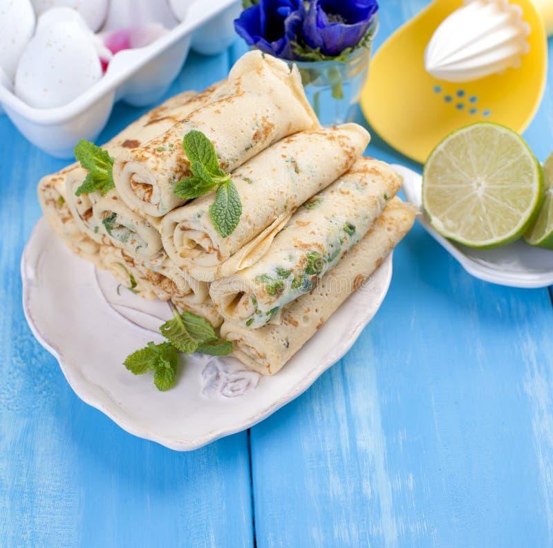 Crepes hechas en casa con la menta y la cal Pasteles rusos tradicionales de la primavera Desayuno delicioso de la familia que coc imagen de archivo