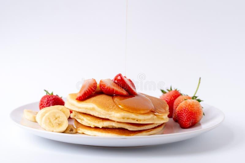 Crepes hechas en casa con las fresas y plátano y miel frescos de la rebanada en la placa blanca, desayuno sano imagenes de archivo