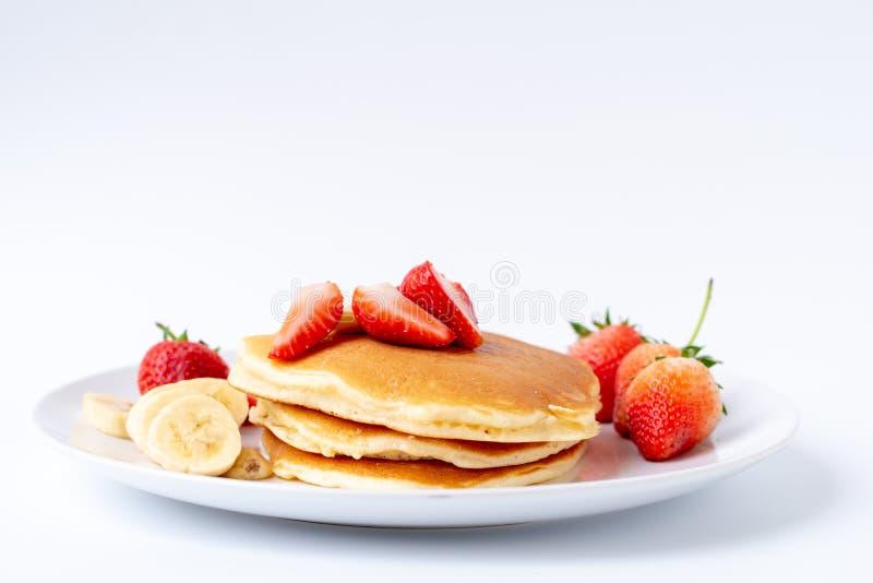 Crepes hechas en casa con las fresas y plátano y miel frescos de la rebanada en la placa blanca, desayuno sano fotografía de archivo libre de regalías