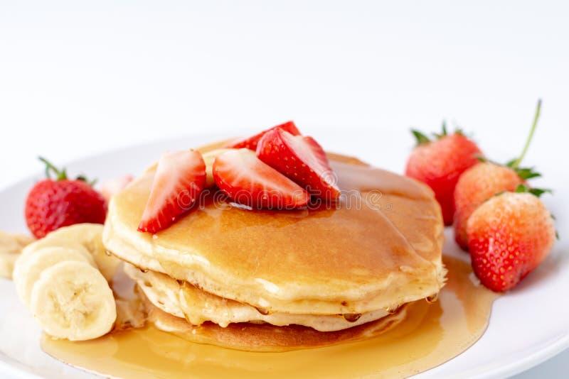 Crepes hechas en casa con las fresas y plátano y miel frescos de la rebanada en la placa blanca, desayuno sano imagen de archivo libre de regalías