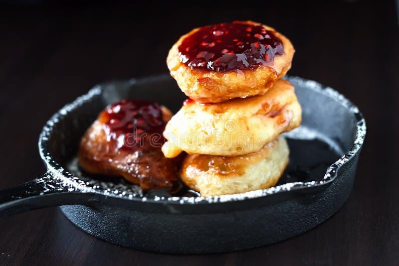 Crepes hechas en casa rusas de la levadura de la pila con el atasco de frambuesa en sartén del arrabio  Concepto del desayuno foto de archivo libre de regalías