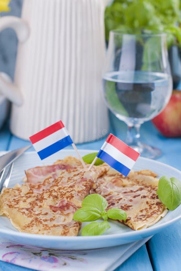 Crepes holandesas con el jamón para los colores brillantes del desayuno, fondo azul Sabroso y calórico imagen de archivo libre de regalías