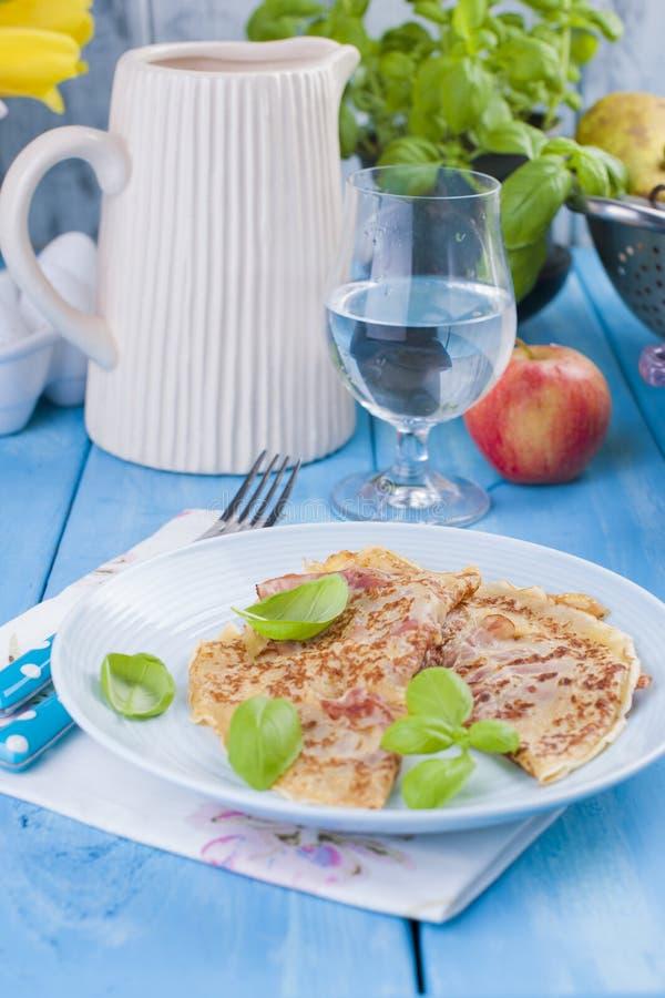 Crepes holandesas con el jamón para los colores brillantes del desayuno, fondo azul Sabroso y calórico Un vidrio del agua y de un foto de archivo libre de regalías