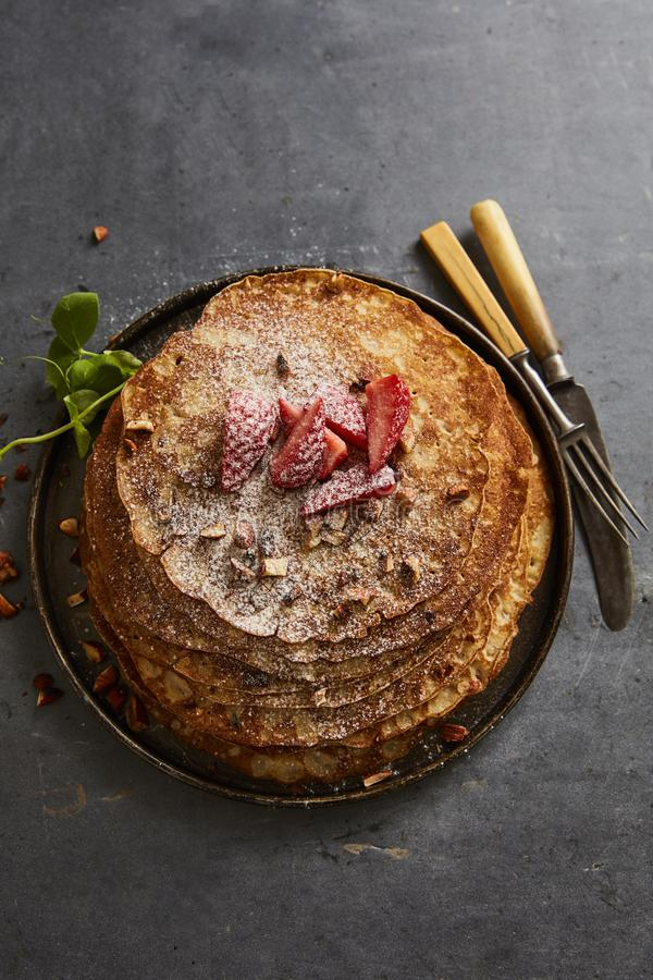 Crepes with strawberries and castor sugar. Homemade crepes with castor sugar, roast almonds and fresh strawberries stock image