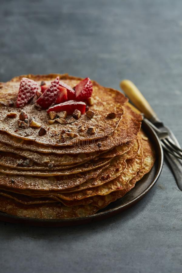 Crepes with almonds, strawberry and castor sugar stock photography