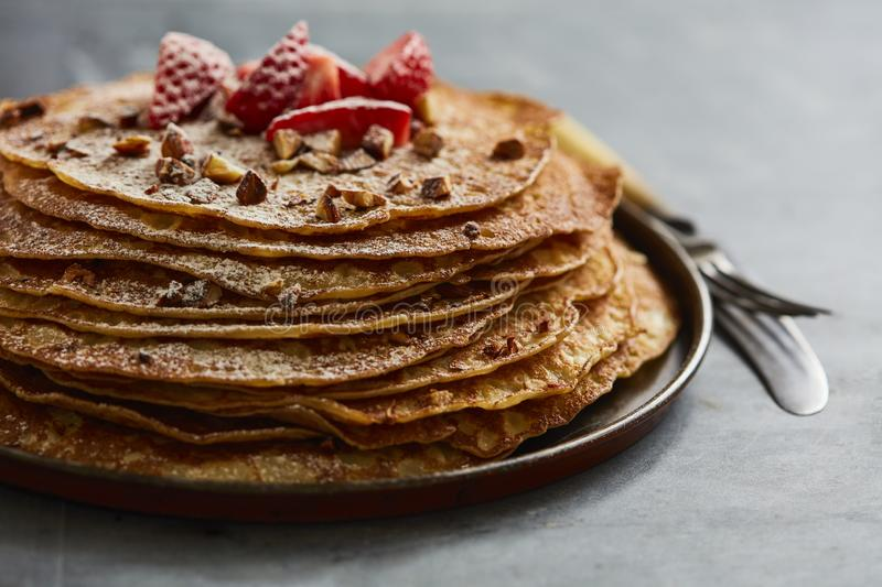 Crepes with strawberries and castor sugar. Homemade crepes with castor sugar, roast almonds and fresh strawberries stock images