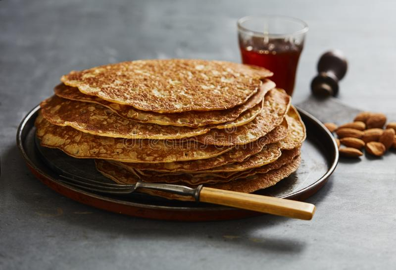Crepes in a heap with maple syrup in a glass by the side stock image