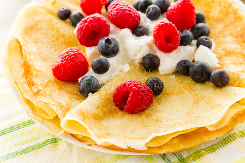 Crepes. Homemade crepes with fresh raspberries and blueberries royalty free stock images