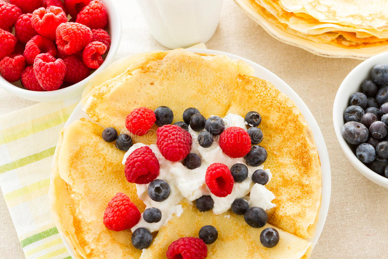Crepes. Homemade crepes with fresh raspberries and blueberries royalty free stock photos