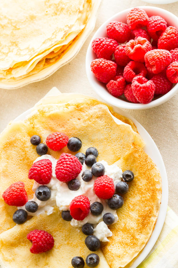 Crepes. Homemade crepes with fresh raspberries and blueberries royalty free stock photography