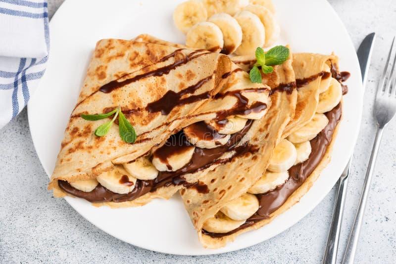 Crepes ou blini enchidos com chocolate, banana imagens de stock
