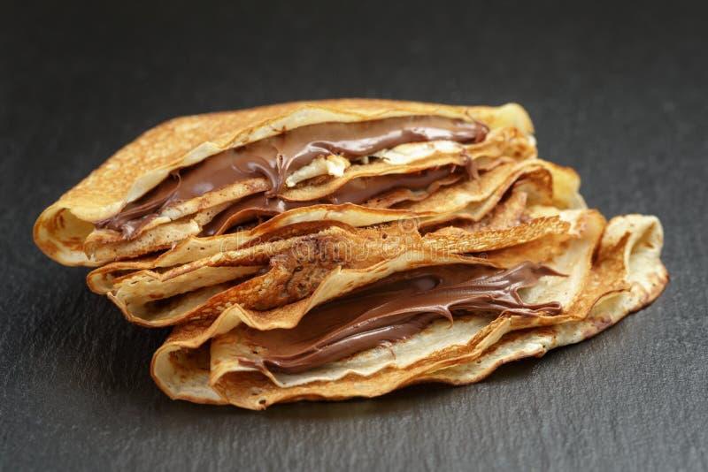 Crepes ou blinis finos com creme do chocolate sobre imagem de stock royalty free