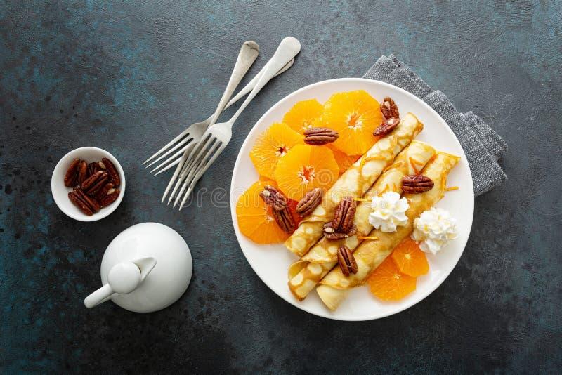Crepes, panquecas finas com fatias de tangerina frescas, nozes de pecan, xarope e nata chicada fotografia de stock