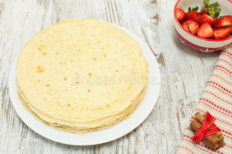 Crepes on plate with ingredients and strawberry. Pile of pancake and ingredient. Fresh homemade crepes on plate with ingredients and strawberry, Above view stock photography