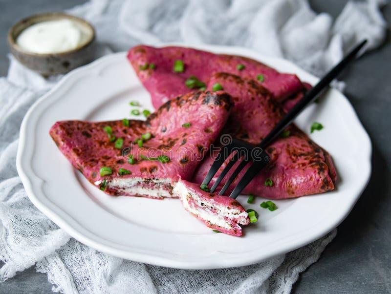 Crepes rojas de las remolachas, crespones finos rosados de la remolacha rellenos con el queso cremoso y cebollas verdes en fondo  fotografía de archivo libre de regalías