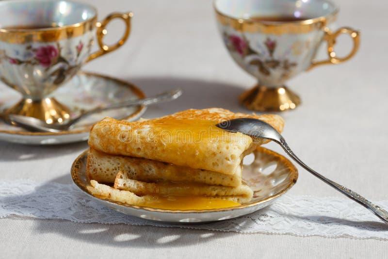 Crepes rusas con la miel y la taza de té fotos de archivo