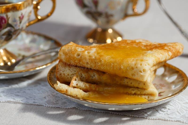 Crepes rusas con la miel y la taza de té fotos de archivo libres de regalías