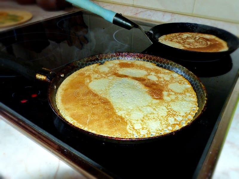Crepes rusas tradicionales del blini en un sartén del arrabio Cocinar el blinov Semana de la crepe Maslenitsa imagen de archivo libre de regalías