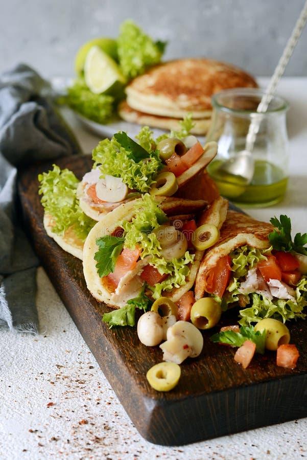 Crepes sin azucarar con el pavo, la lechuga, tomates, setas conservadas en vinagre, aceitunas y verdes bajo la forma de tacos en  foto de archivo libre de regalías