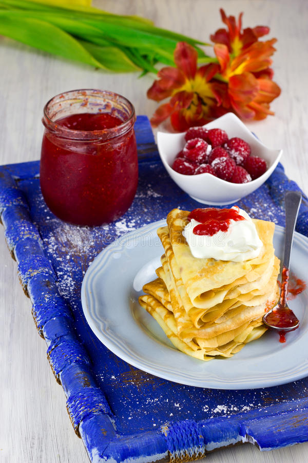 Crepes With Sour Cream and Homemade Strawberry Jam. Crepes With Sour Cream and Homemade Strawberry Confiture On Old Blue Wooden Tray royalty free stock photo