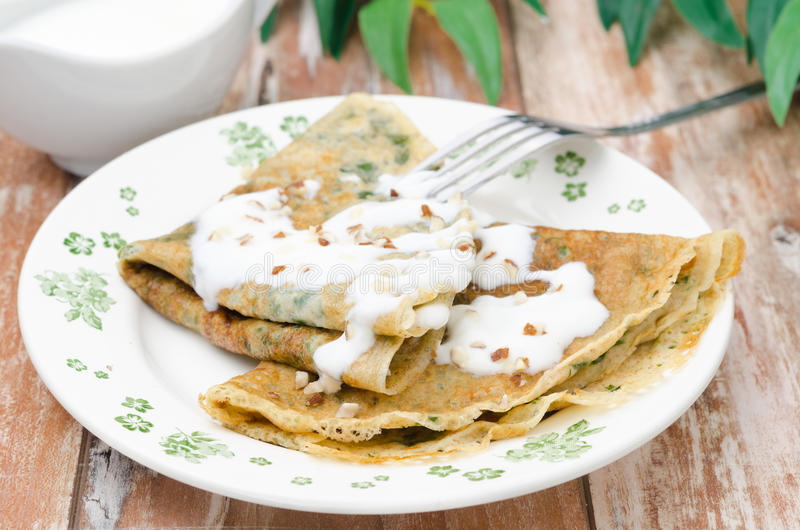 Crepes with spinach with yogurt sauce and nuts royalty free stock images