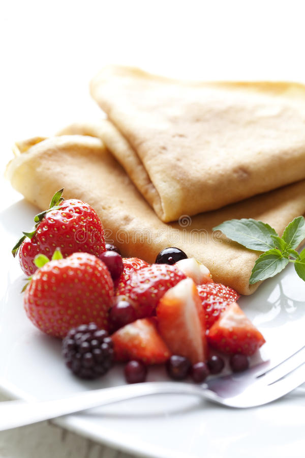 Crepes with strawberries. Sweet thin french style crepes, served with strawberries and castor sugar, very close up and very shallow dof for a dreamy effect stock images