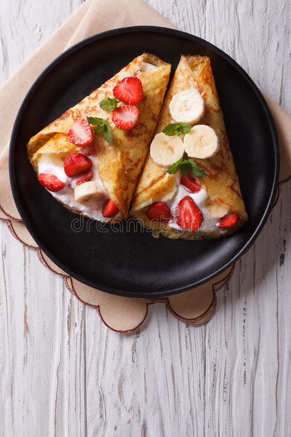 Crepes with strawberries, bananas and cream vertical top view. Homemade crepes with fresh strawberries, bananas and cream on a plate. vertical top view stock photos
