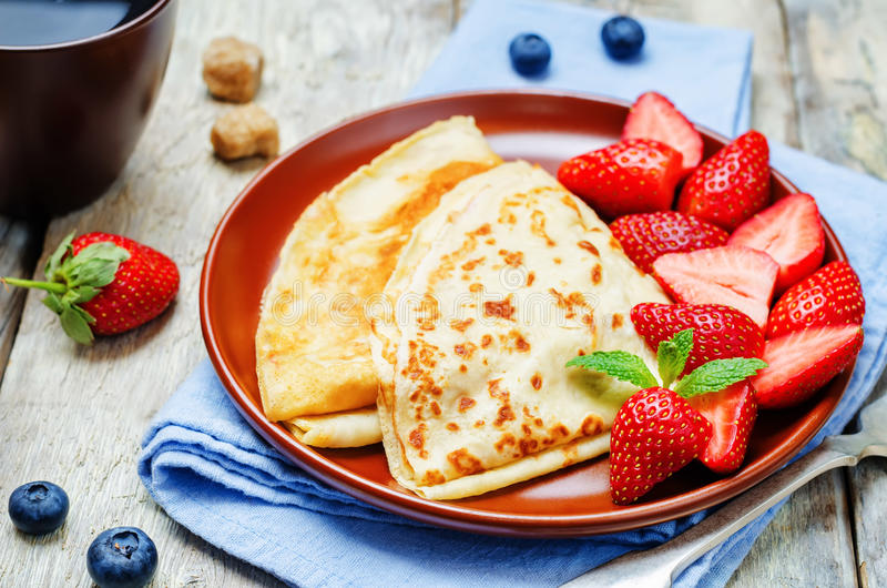 Crepes with strawberries. On a wood background. toning. selective focus royalty free stock photos