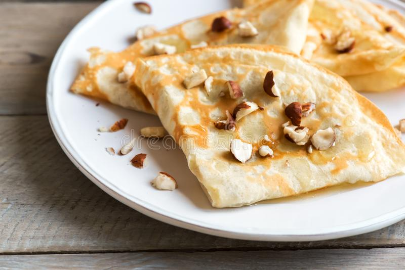 Crepes. Suzette with honey and nuts on white plate over wooden background, copy space. Delicious homemade  for breakfast stock photography