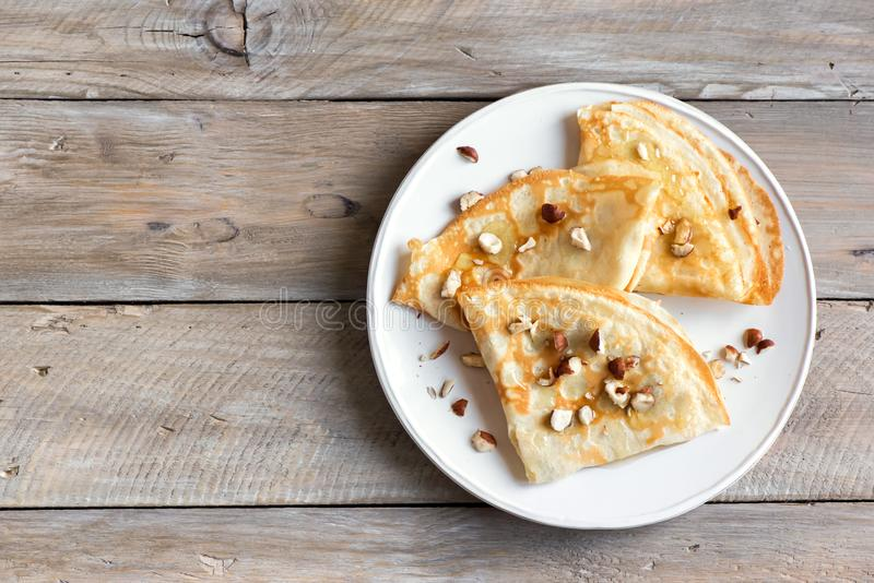 Crepes. Suzette with honey and nuts on white plate over wooden background, copy space. Delicious homemade  for breakfast stock images