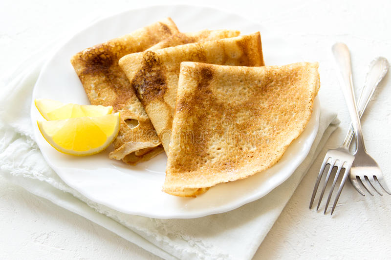 Crepes. Suzette with lemon on white plate over white background, copy space. Delicious homemade  for breakfast stock photos