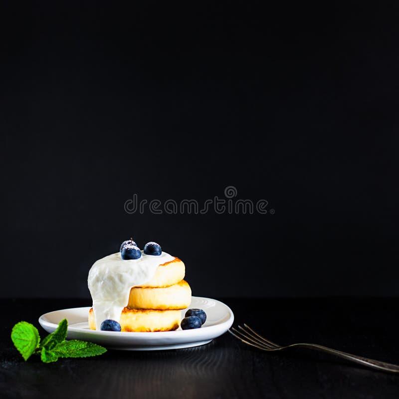 Crepes una del requesón en otro rematado con crema, los arándanos y el polvo del azúcar en fondo negro con la bifurcación y el ve imagenes de archivo