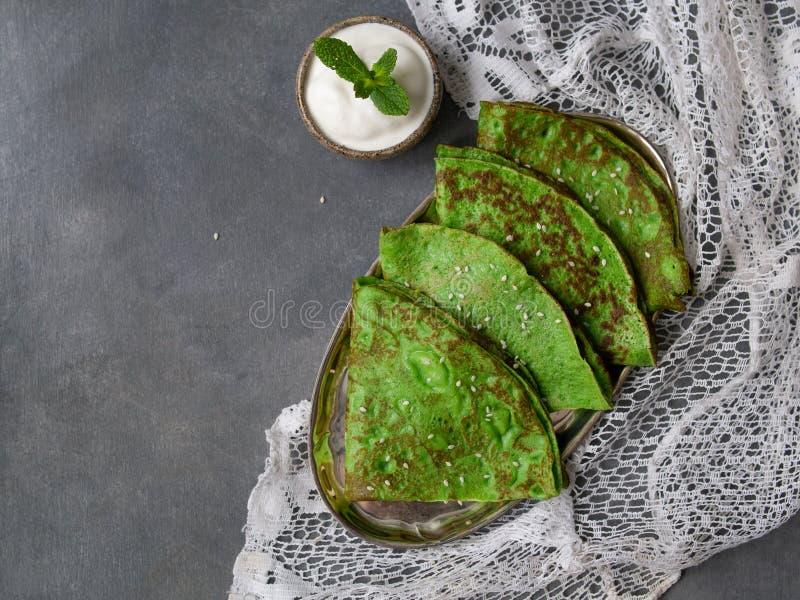 Crepes verdes da hortelã com a folha do creme de leite e da hortelã na placa de metal no fundo cinzento com tela do laço feche ac imagens de stock