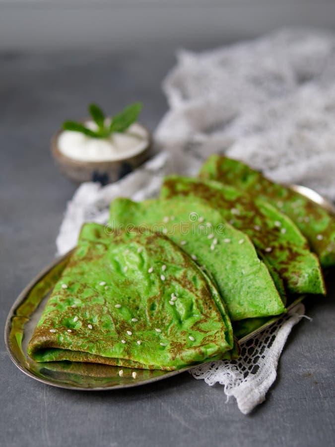 Crepes verdes da hortelã com a folha do creme de leite e da hortelã na placa de metal no fundo cinzento com tela do laço Perto ac imagem de stock