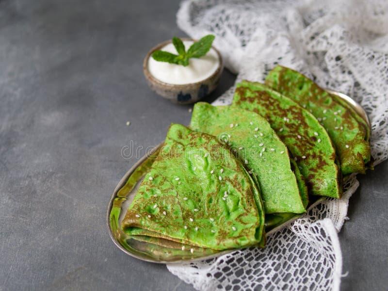 Crepes verdes da hortelã com a folha do creme de leite e da hortelã na placa de metal no fundo cinzento com tela do laço Perto ac imagens de stock