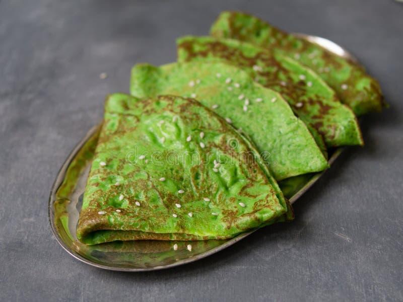 Crepes verdes da hortelã na placa de metal no fundo cinzento Feche acima, foco seletivo Café da manhã gourmet Maslenitsa Crepes f fotografia de stock