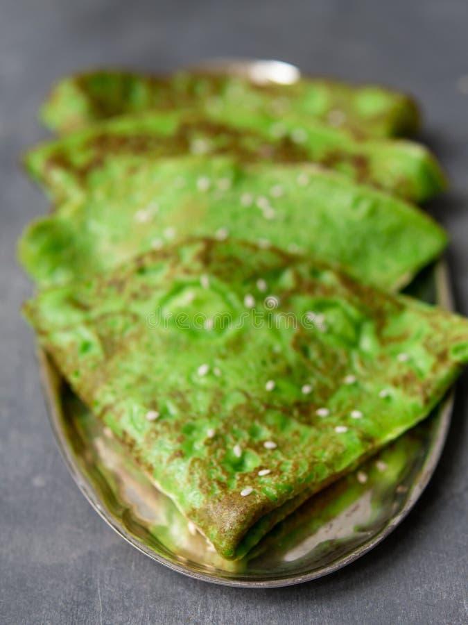 Crepes verdes da hortelã na placa de metal no fundo cinzento Feche acima, foco seletivo Café da manhã gourmet Maslenitsa Crepes f foto de stock