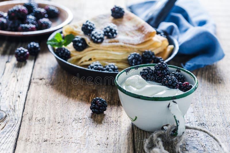 Crepes,yogurt in rural mug, fresh blackberries, healthy breakfast. Healthy breakfast or brunch, favorite morning meal. Homemade crepes, fresh summer blackberry stock photos