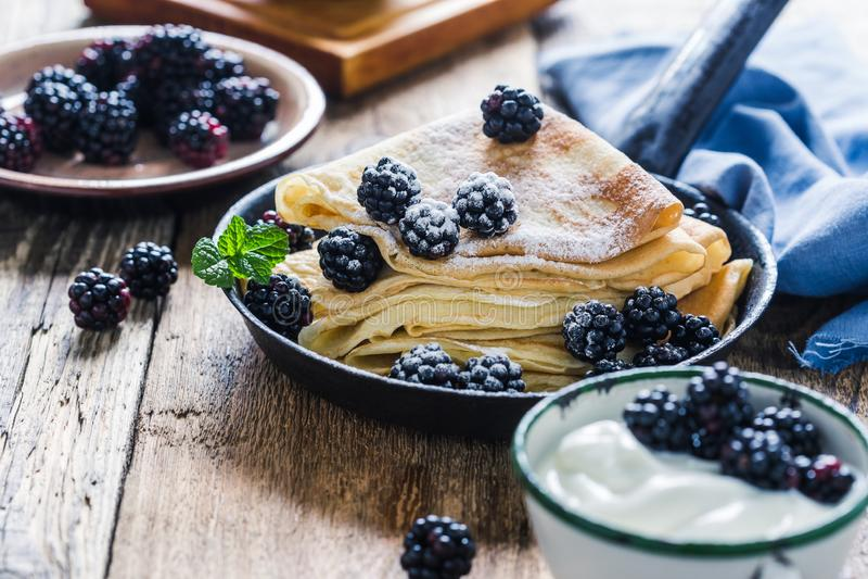 Crepes,yogurt in rural mug, fresh blackberries, healthy breakfast. Healthy breakfast or brunch, favorite morning meal. Homemade crepes, fresh summer blackberry royalty free stock photo