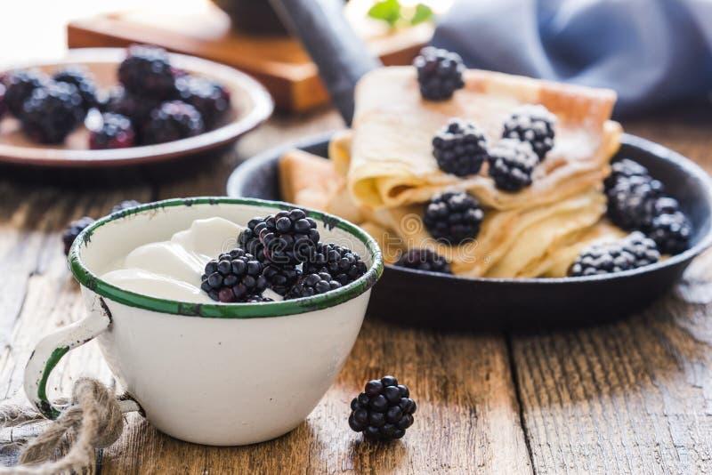 Crepes,yogurt in rural mug, fresh blackberries, healthy breakfast. Healthy breakfast or brunch, favorite morning meal. Homemade crepes, fresh summer blackberry stock photography